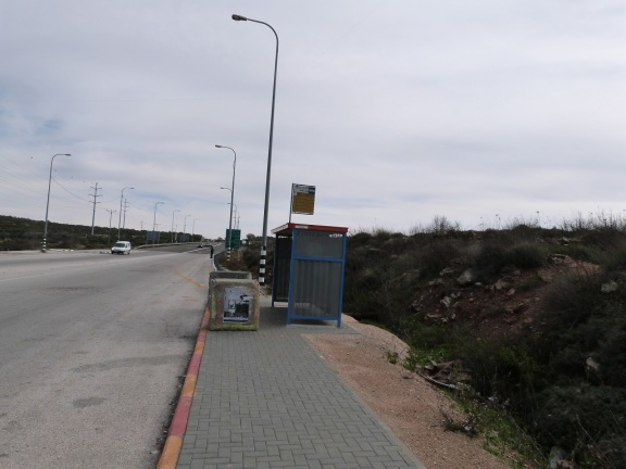 The 'Settler' bus stop at Za'atar. A Palestinian man waits by the roadside in the far distance.