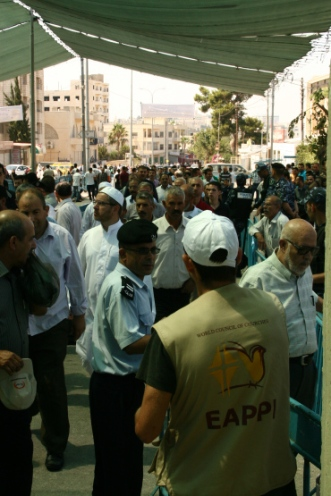 An EA looks on at the masses gathering to go to Friday Prayers. Over 22,300 people crossed the Bethlehem Checkpoint on the first Friday of Ramadan.