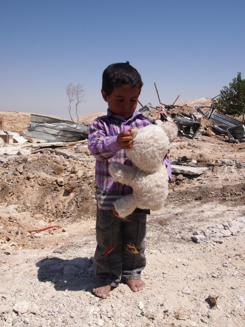 A boy finds his teddy bear. Photo EAPPI/J. Kaprio