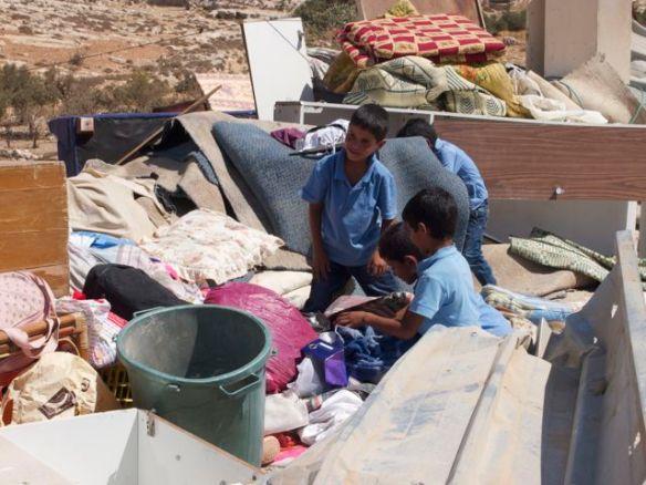 Boys rummage through rubble in search of their toys. Photo EAPPI/J. Kaprio