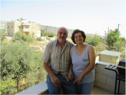 George and Sylvia Handal. The separation wall is built next to their house in the distance. Photo EAPPI/C. Jones