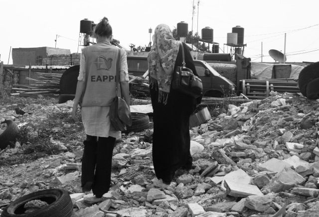 An EA walks with a woman from Nabi Samwil at the site where her home was demolished. Photo EAPPI/M. McGivern, 2011.