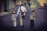 An Israeli settler walks with his children while carrying a gun on Shuhada street. Photo EAPPI/D. Wach, 2013.