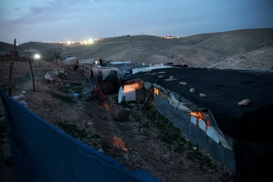 Homes in Khan Al Ahmar. Lights from the nearby settlement can be seen on the hill. Photo EAPPI/K. Ranta.