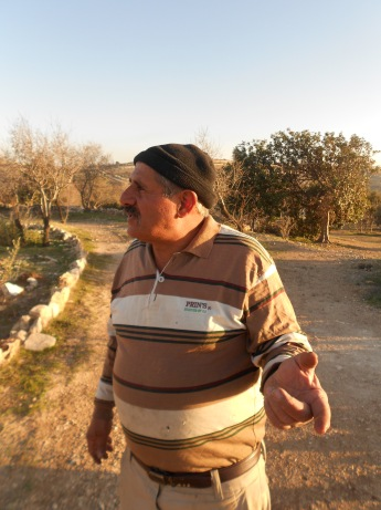 Daher Nassar points to one of the surrounding Israeli settlements. Photo EAPPI/E. Goebel.