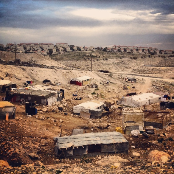 Bedouin homes with canvas roofs lie in the foreground, while in the distance red tiled settlement houses lie in neat tiers. Unpaved dirt roads serve the Bedouin communities of the Jerusalem periphery as the Israeli authorities refuse to recognise their camps and provide them with necessary infrastructure and services. However, the surrounding settlements, recognised as illegal under international law by the international community, enjoy developed infrastructure, access to medical, electricity and water services, paved roads and funded schooling. The juxtaposition is quite stark. Photo EAPPI/K. Ranta.