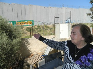 Antoinette points out the separation wall in front of her home. The wall now cuts her off from accessing Jerusalem. Photo EAPPI/L. Hilton,