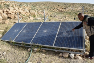 Acmad inspects the broken solar panels. Photo EAPPI/V. Rochat.