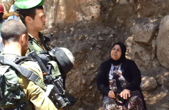 Ferial Abu Haikal discusses with Israeli soldiers. Photo EAPPI/W. Bischler.