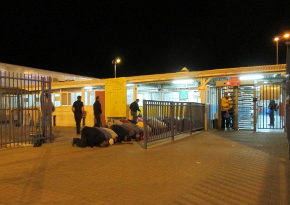 Despite the long, daily waits, many men waiting in the queue stop to pray on the Jerusalem side of the checkpoint before loading the buses to work. Photo EAPPI/ B. Currie.