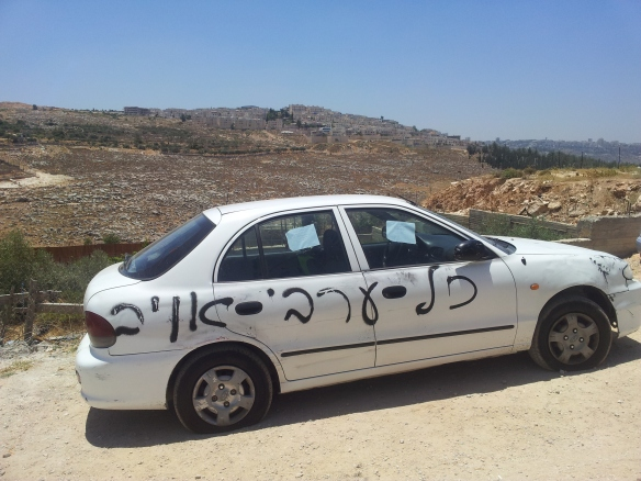 """Muhammed's car where Israeli extremists have slashed the tires and written, """"All Arabs are the enemy"""", in the background an Israeli settlement. Photo EAPPI/D. Jakobsson."""