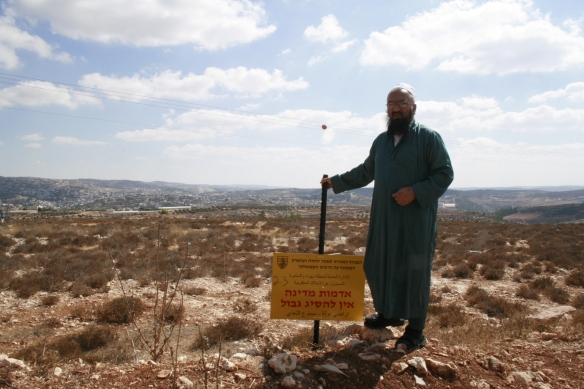 Sheikh Nasser stands next to a sign on his land declaring it as state land.  The Israeli military will not allow him to use this land. Photo EAPPI.