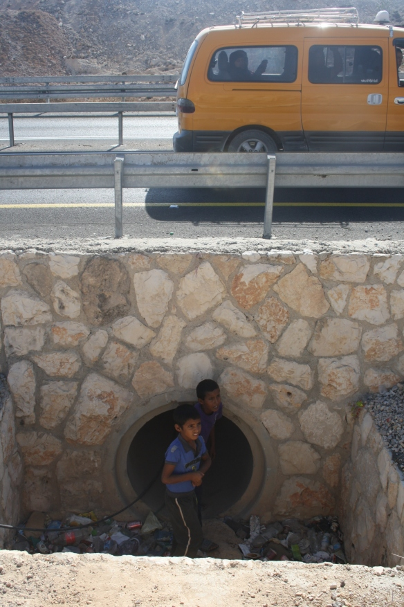 Daod (12) and Ahmad (8) emerge from the pipe under the busy road. Photo EAPPI/ML. Kjellstrom.