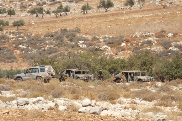 A civilian jeep belonging to an Israeli settler drives past 2 Israeli military jeeps during a training exercise, 10 September 2014. Photo EAPPI/N. Ray.