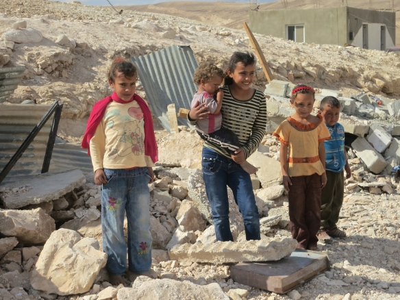 Children stand in their demolished home.