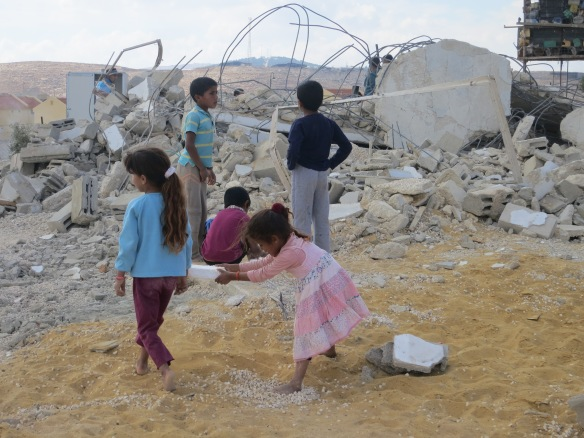 Children play near ruins of demolished buildings.