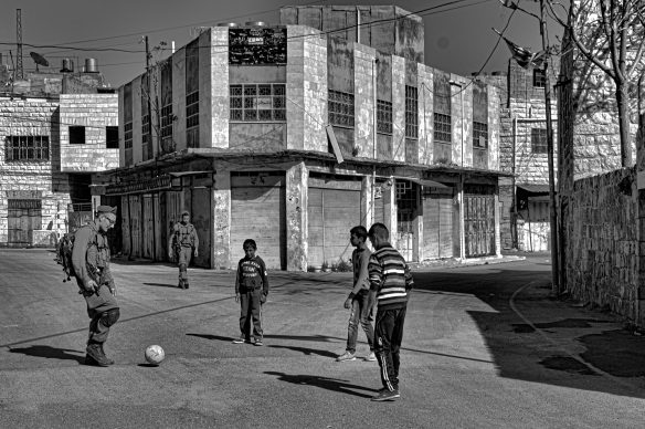 March 2015. West Bank, Hebron. Palestinian children playing with an Israeli soldier. Photo EAPPI, M. Guntern