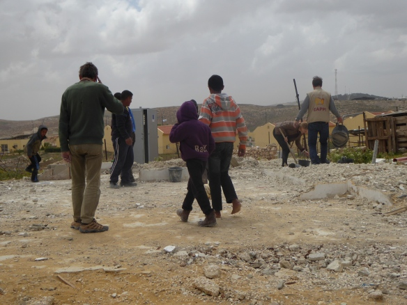 EAs and local residents clearing demolition rubble in Um al Kher South Hebron Hills  Photo EAPPI/P Moore 2015