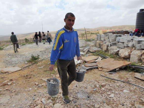 Al Mukhtasem Hathaleen carrying rubble from site of demolished house at Land Action in Um al Kher, South Hebron Hills  Photo EAPPI/P Moore 2015