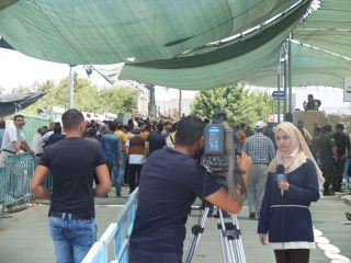 03.07.15. Bethlehem. Checkpoint 300 during third Friday of Ramadan. Palestinian TV crew reporting from the men's gate. Photo EAPPI