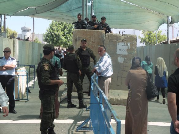 03.07.15. Bethlehem. Checkpoint 300 during third Friday of Ramadan. Security set up with Palestinian police (foreground) and Israeli border police (above). The Wall (background). Photo EAPPI