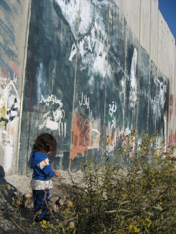 01.01.2014 Bethlehem. Child and the wall next to Ayda camp. Photo EAPPI
