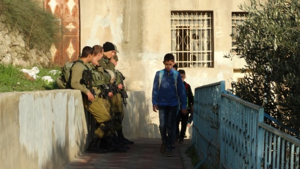 19.11.15_Hebron_School boy passing soldiers Cordoba school run_EAPPI_Hannah Griffiths_small (1)