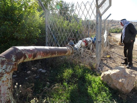 09.12.15. Baddala Village. Jordan Valley, Palestine. Abdulla Sawafta examines the Israeli freshwater supply pipework. Photo EAPPI/ P. Longden