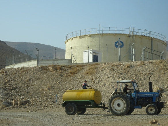 21.12.15. North Jordan Valley, Palestine. Tractor delivering water to a Palestinian community (Israeli water tank in the background) Photo EAPPI/P. Longden
