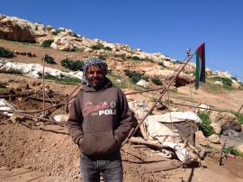 05.02.16. Ali in front of the remains of his tent. Photo EAPPI/ M. Mowe
