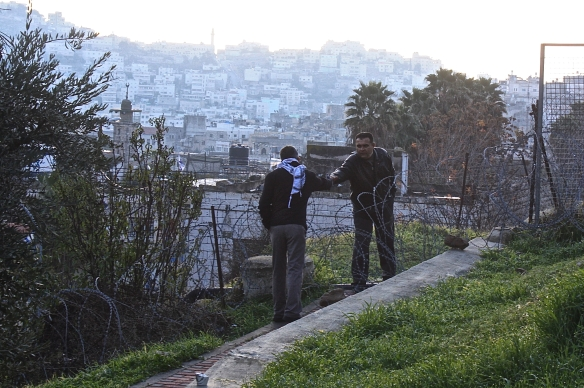 14.12.15_Hebron_People shaking hands over razor wire close to Cordoba school_EAPPI_S.Villpponen