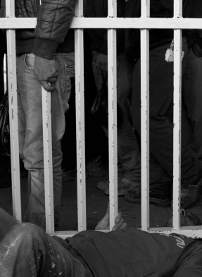 01.02.16. CP300. A friend helps a man crawl under the gate of 'the cage' area of the checkpoint. Photo EAPPI/P. Morgan
