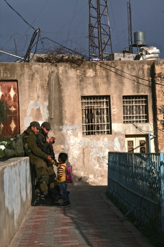 17.11.15_Hebron_School boy greeting soldiers Cordoba school run_EAPPI_Ingrid Stolpestad