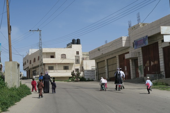 19.03.16, Hebron,3 settler's and Palestinian walk on the opposite side of the road. Settler families are walking because of Shabbat, usually they drive on this road. Photo EAPPI:A. Kaiser