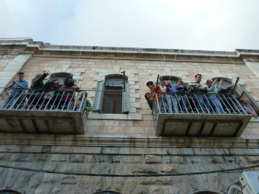6. Residents of the Old City (near Lion's Gate) looking down on the crowds entering the Old City of Jerusalem. Photo EAPPI / C. Merer.