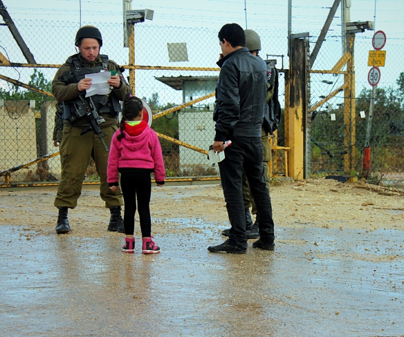 14.3.16, Deir Al Ghusun, Palestinian father and daughter are questioned at the entrance to the seam zone. EAPPI/A. Dunne