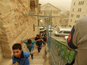 School children running from a settler woman who has harassed Palestinian school children in the past. 08.09.15 Hebron, H2, Shuhada Street. Photo EAPPI/C. Würzberger. 08.09.15